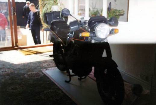 BMW K75 motorcycle in a living room being used as a plant stand.
